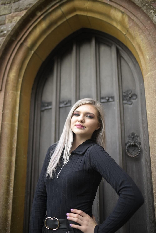 woman in black long sleeve shirt standing beside brown wooden door