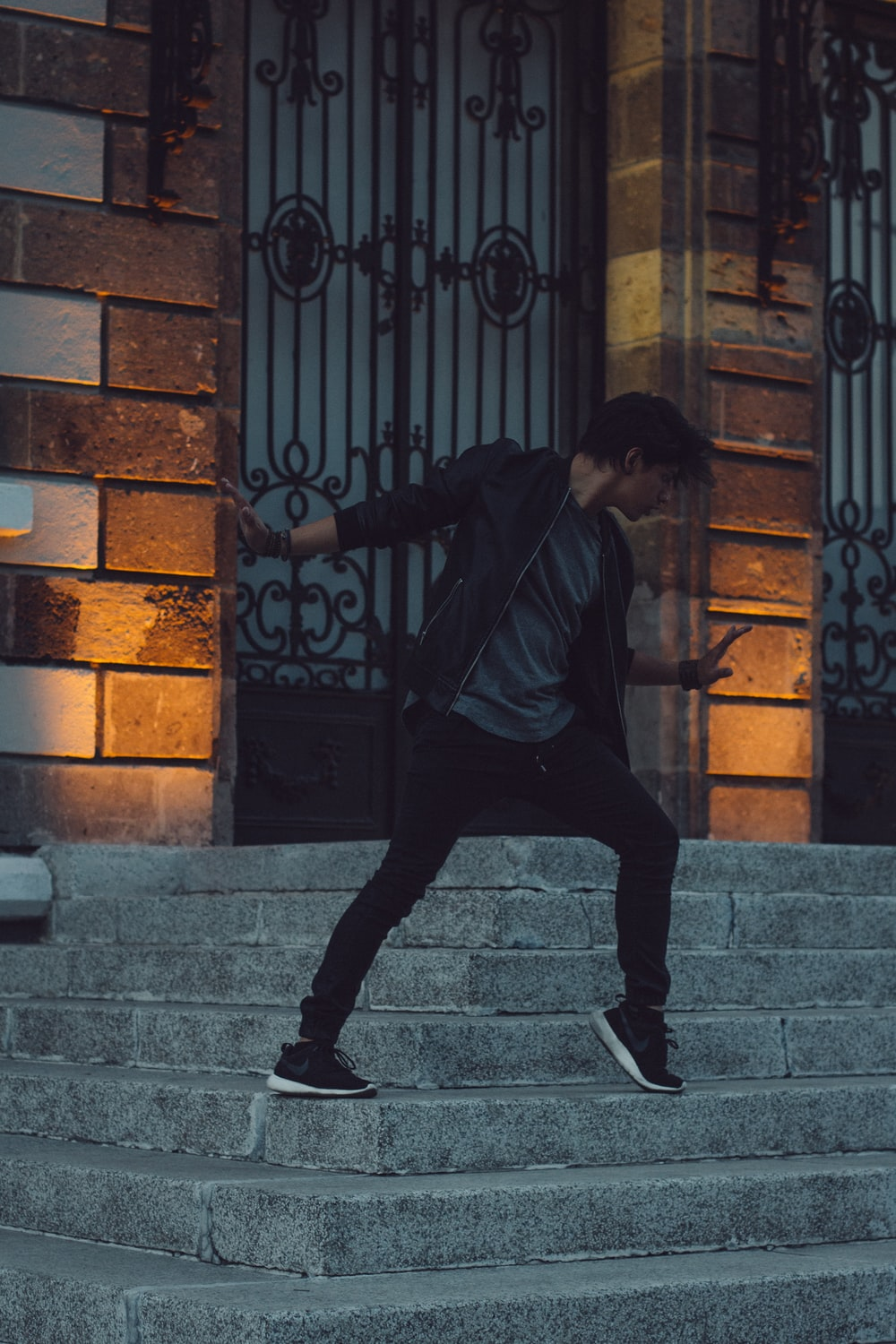 man in black jacket and black pants walking on gray concrete stairs