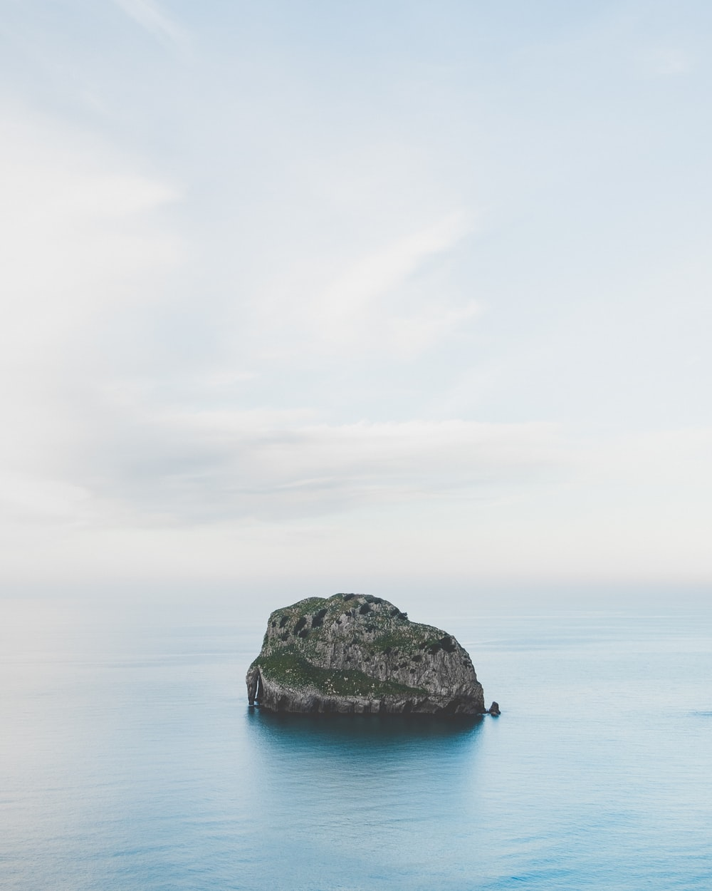 gray rock formation on blue sea under white clouds during daytime