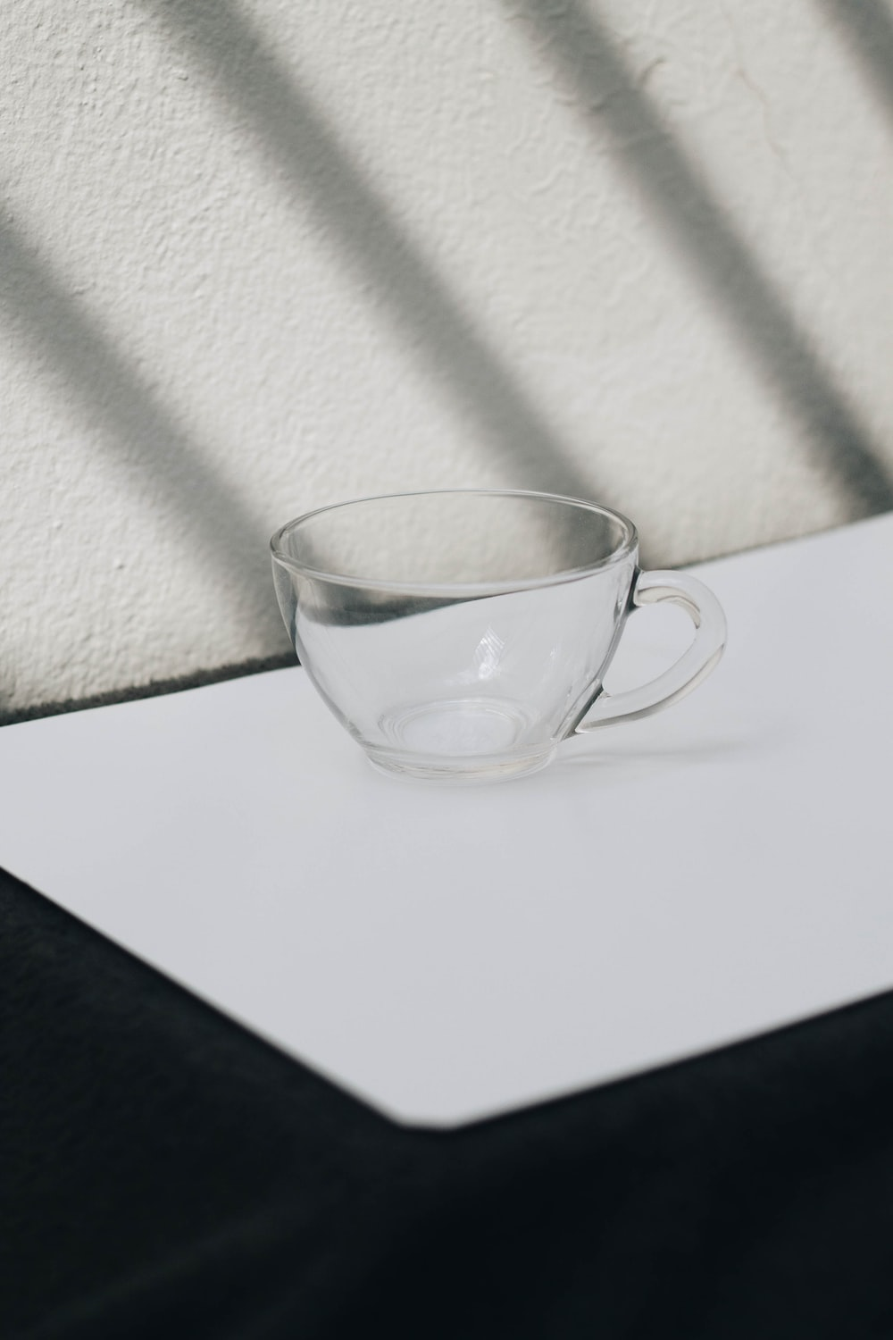 clear glass cup on white table