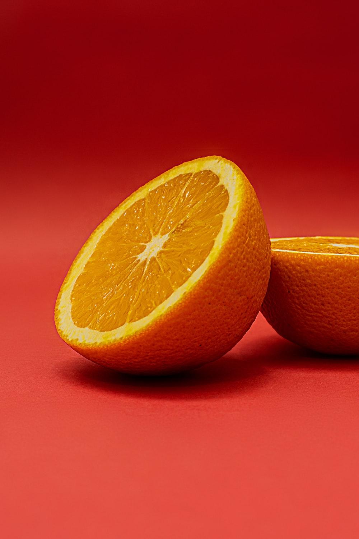 sliced orange fruit on red surface