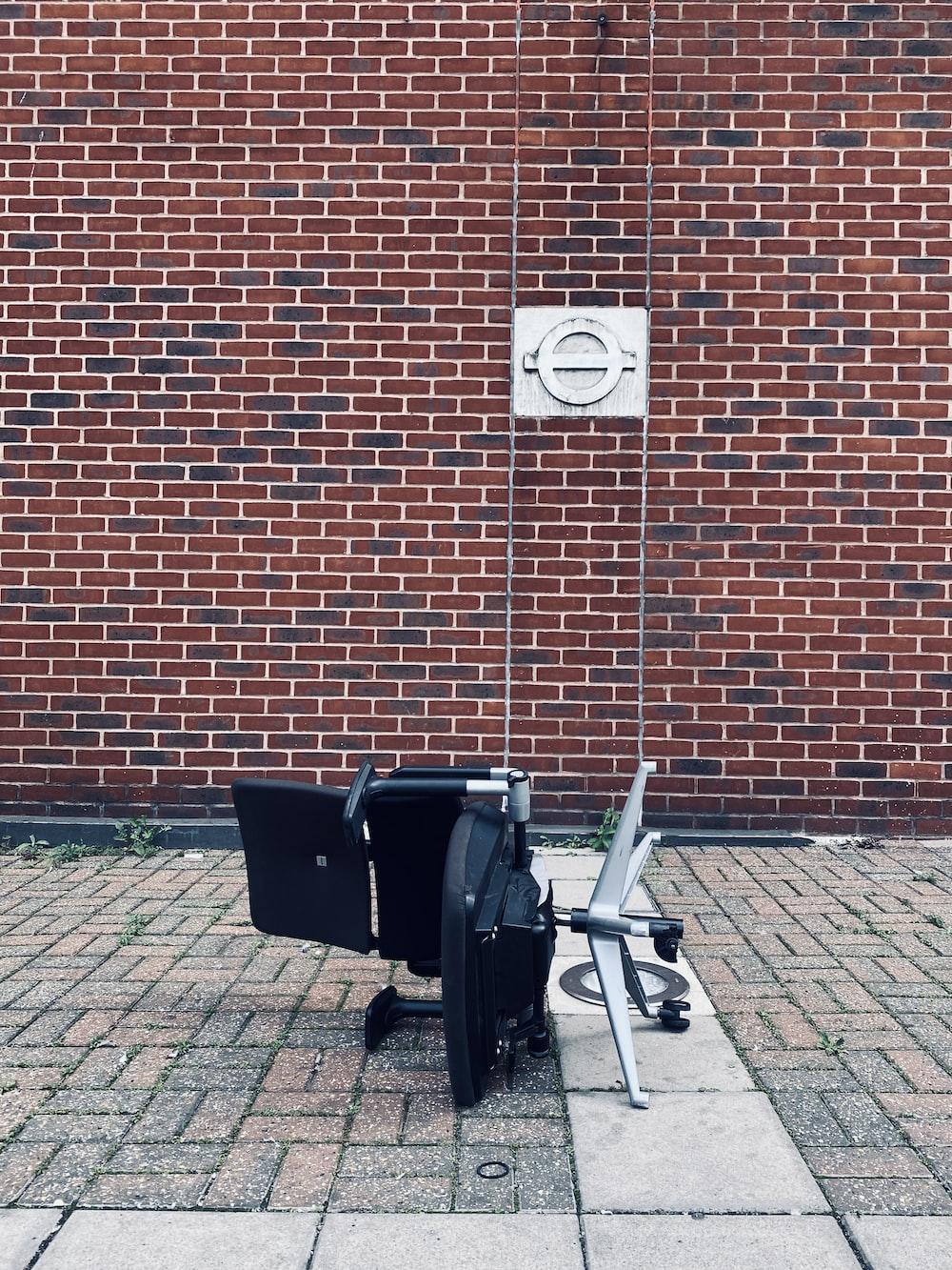 black stroller beside brown brick wall