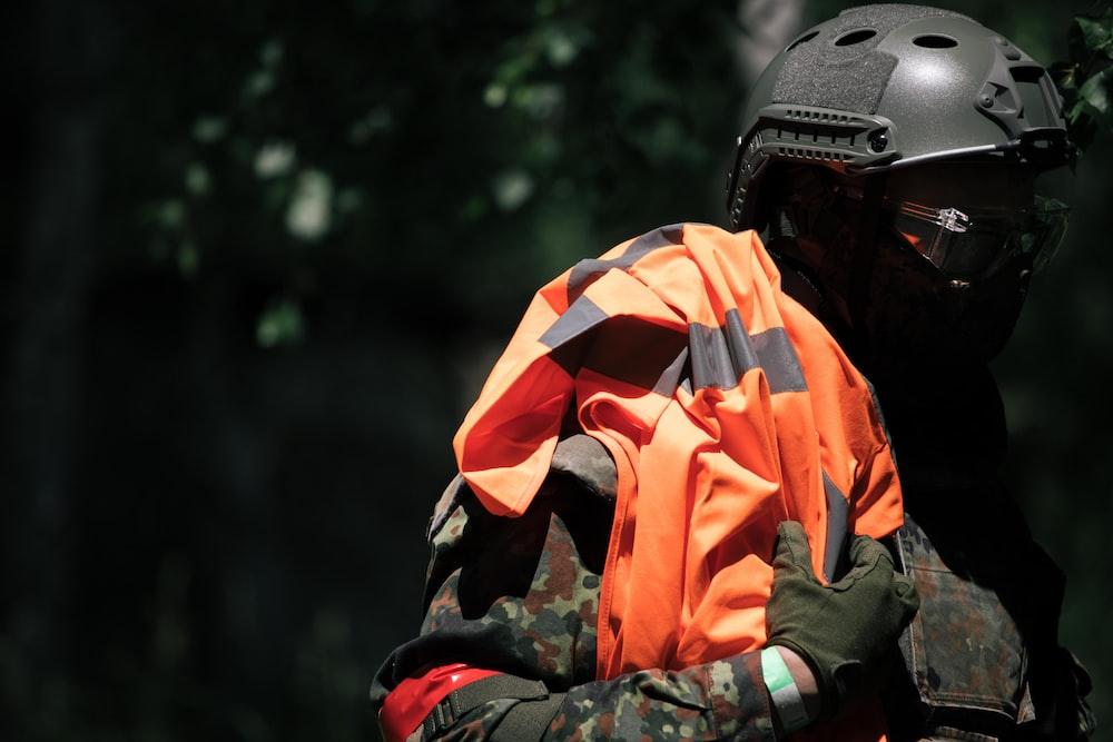 man in orange and black helmet and black helmet