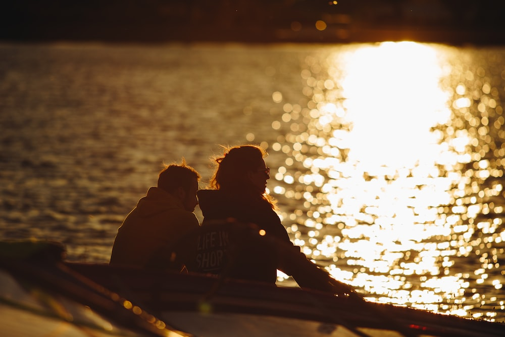 couple sitting on boat during sunset