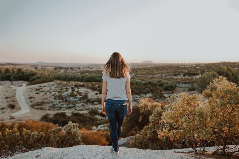 woman in white long sleeve shirt and blue denim jeans standing on gray rock during daytime