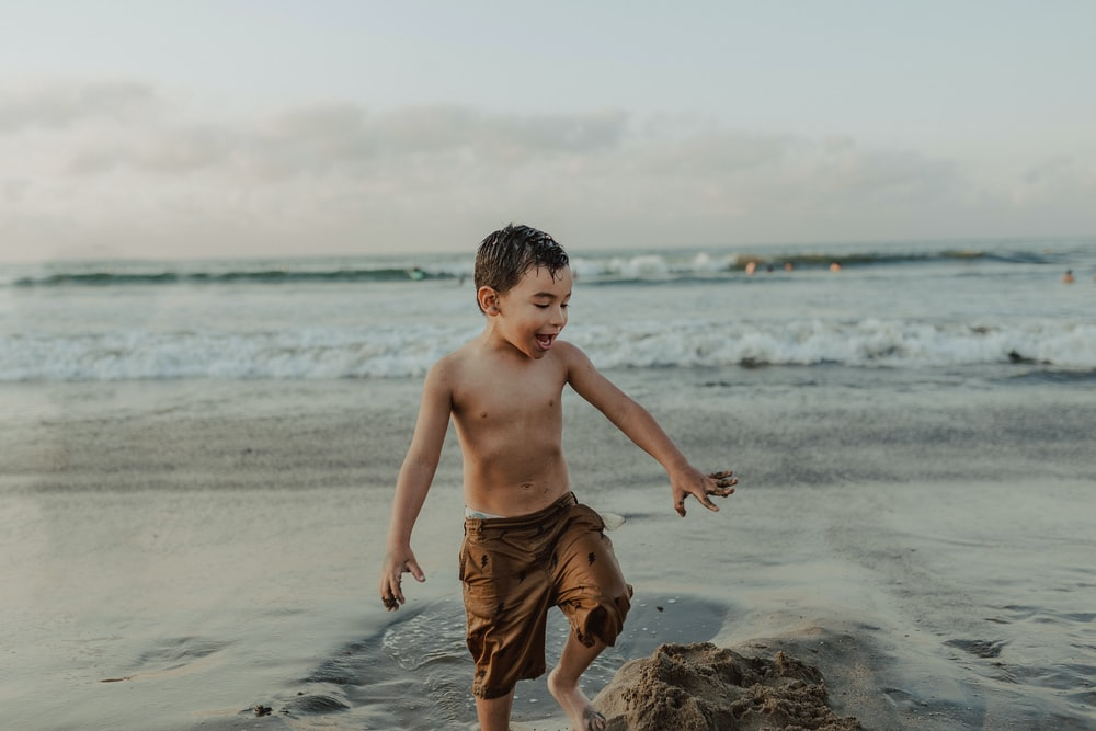 boy in brown shorts standing on beach during daytime