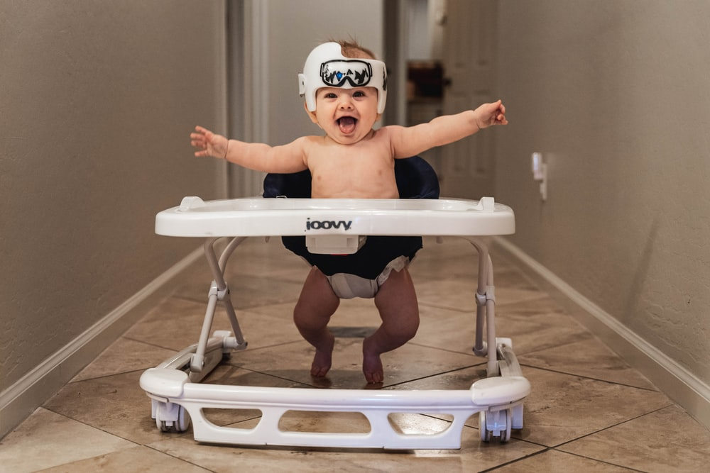 baby in white goggles on white and blue high chair