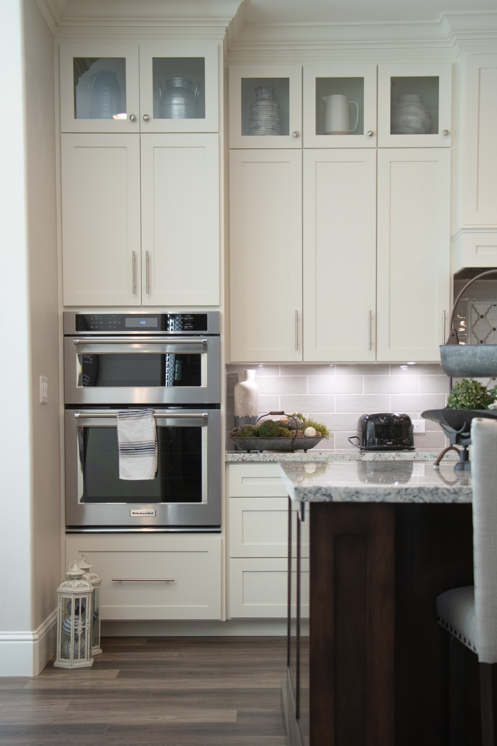 white wooden kitchen cabinet and stainless steel microwave oven