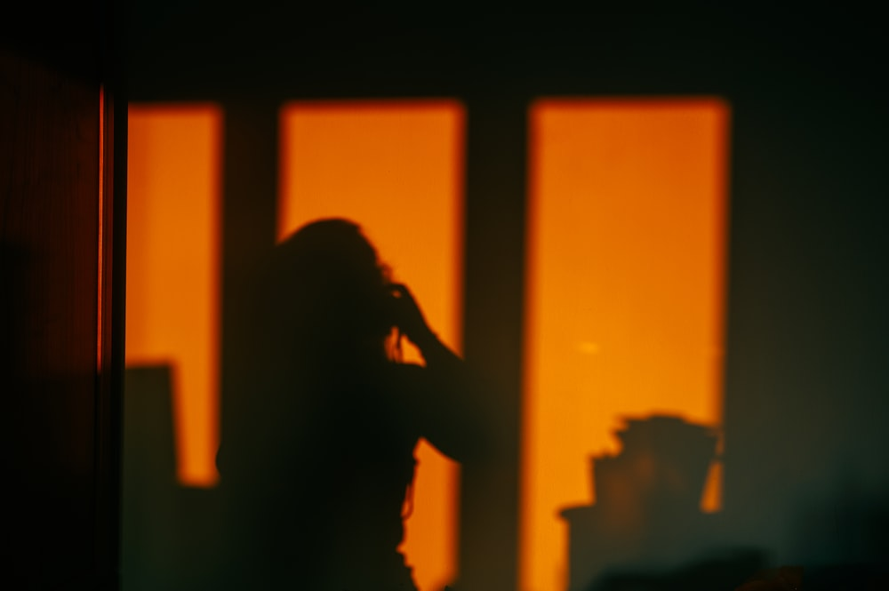 silhouette of woman standing near window