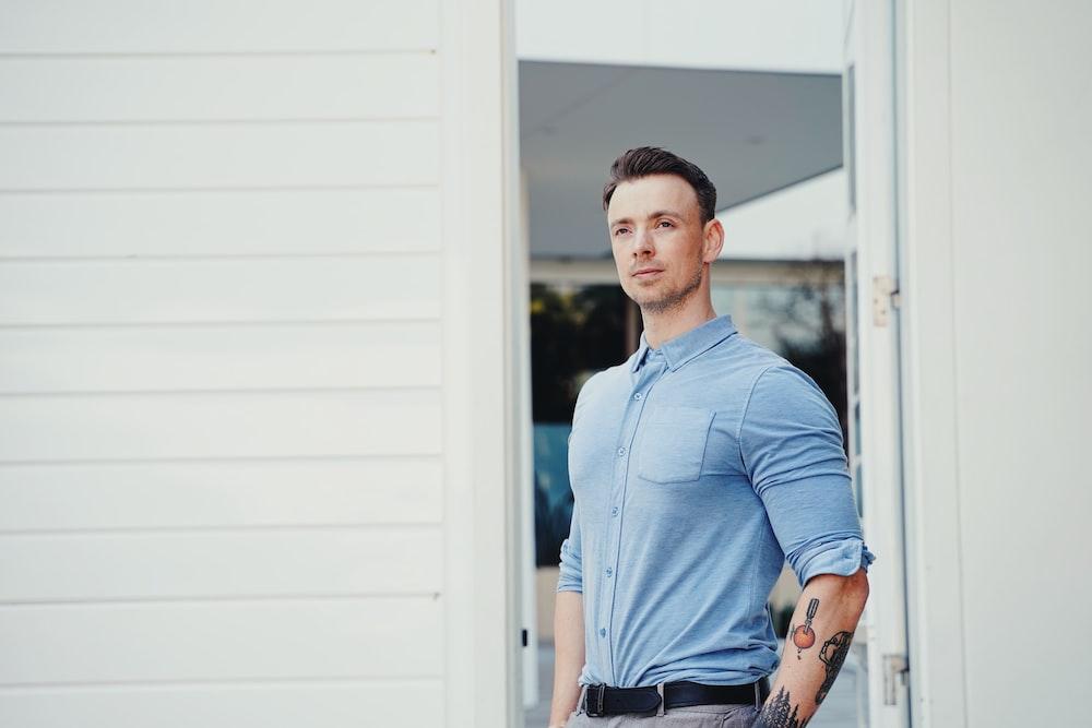 man in blue dress shirt and black pants standing beside white wooden door