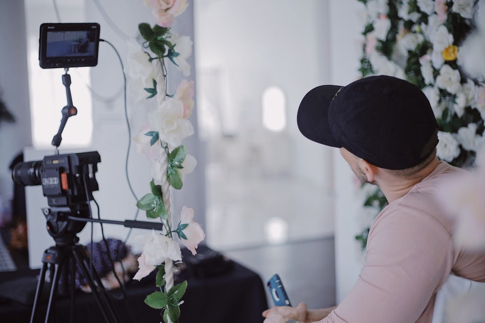 woman in white shirt and black hat holding smartphone