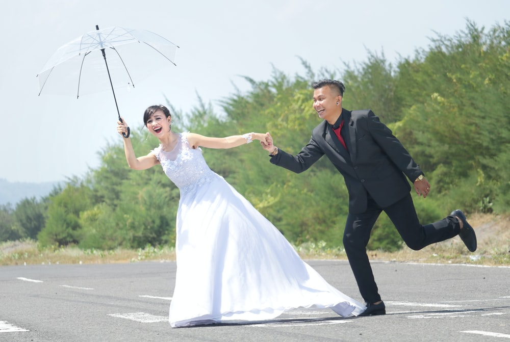 man in black suit holding woman in white wedding dress