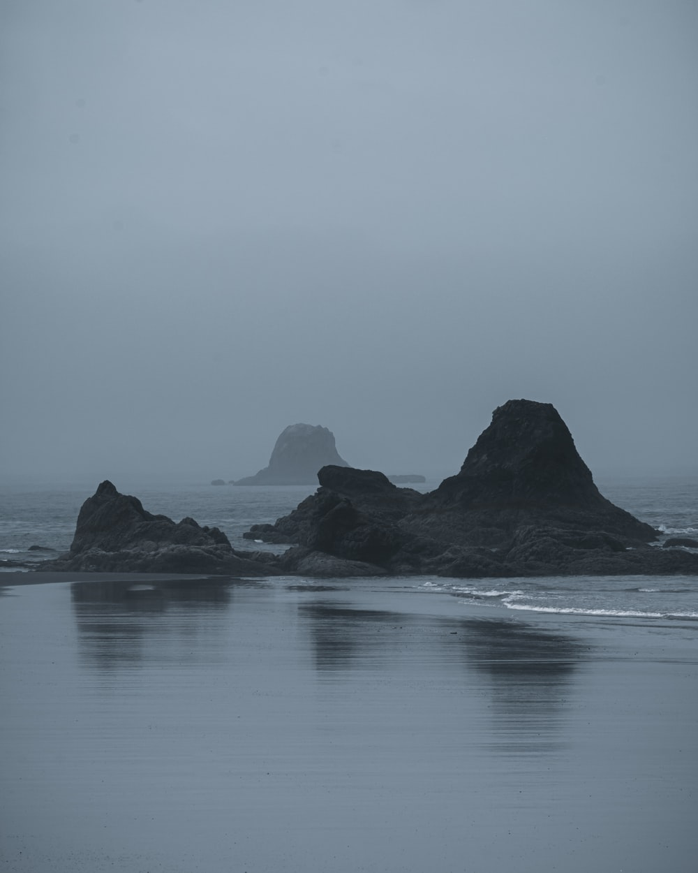 black rock formation on body of water during daytime