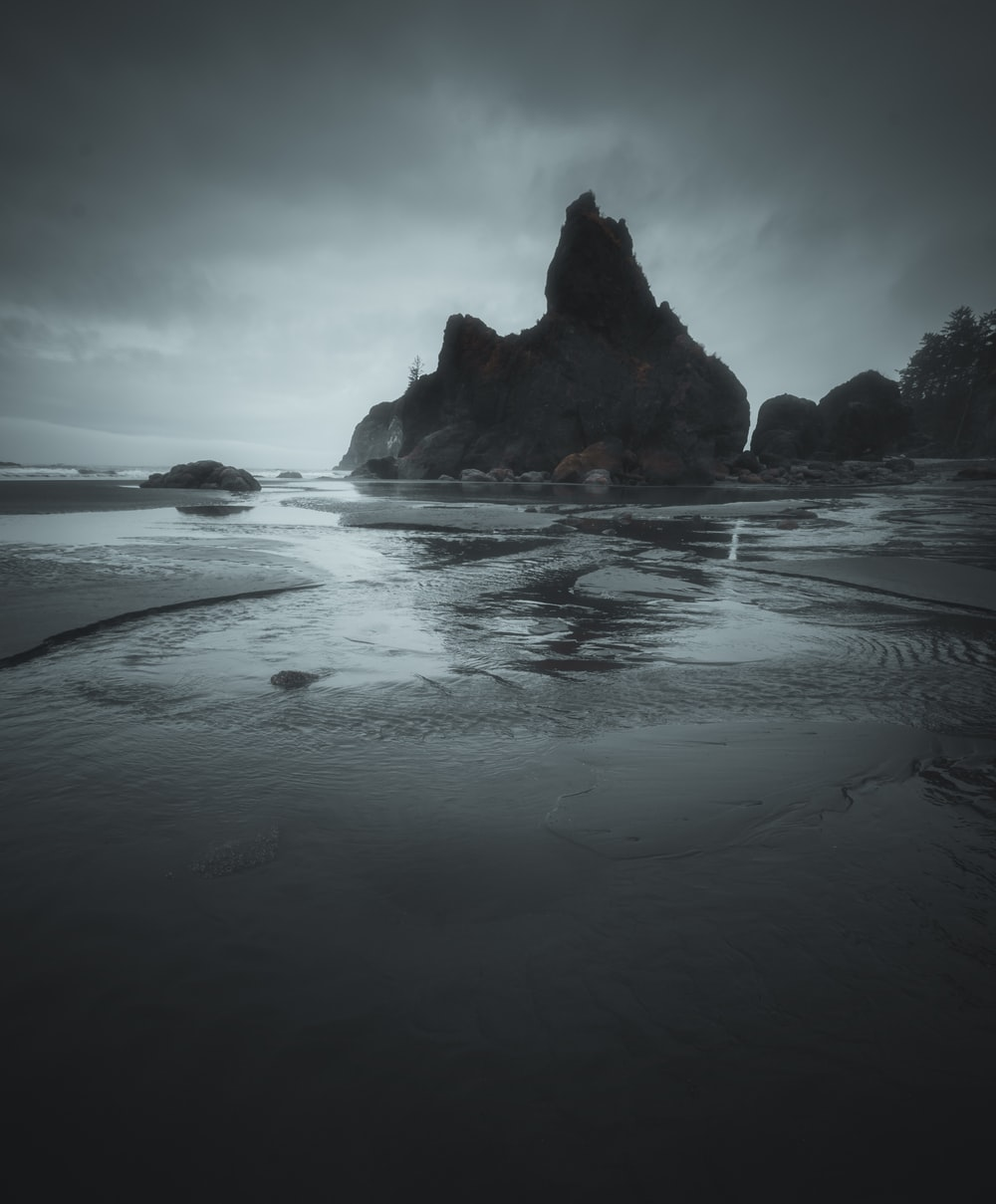 rock formation on body of water under cloudy sky