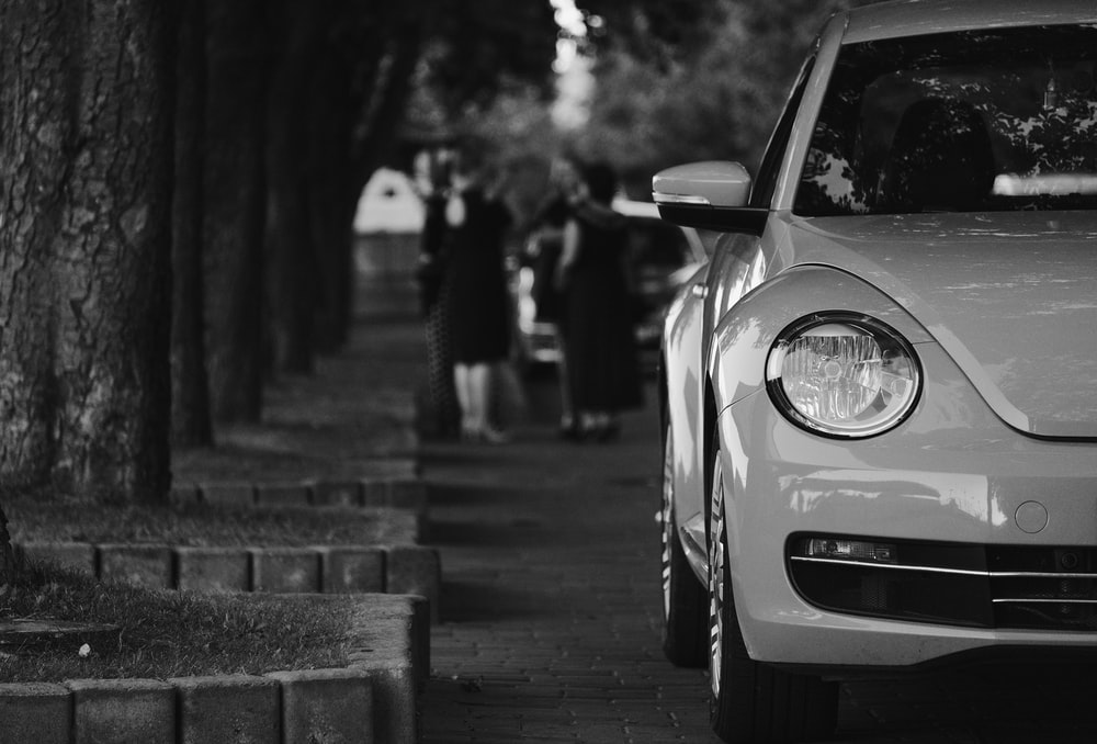 grayscale photo of car parked on sidewalk