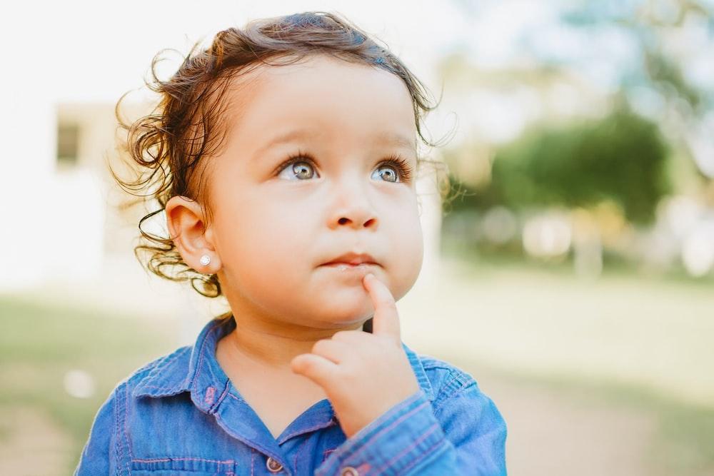 child in blue denim button up shirt