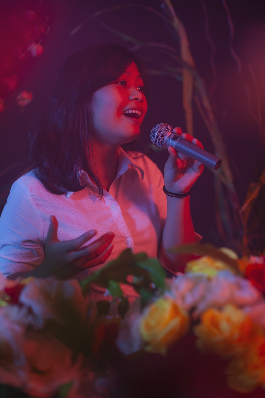 woman in white shirt singing