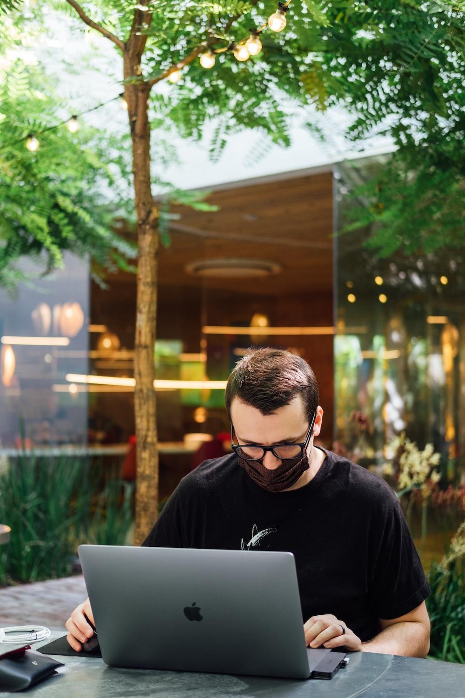 man in black crew neck shirt using macbook