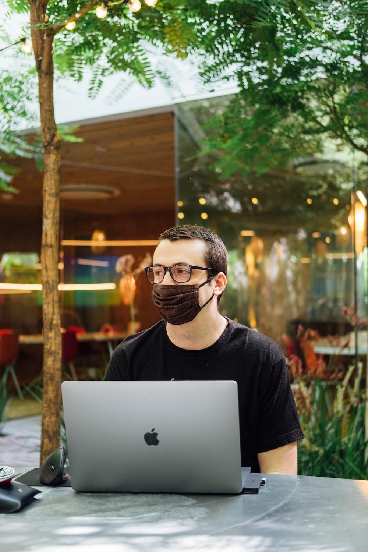 man in black crew neck t-shirt wearing black framed eyeglasses using silver macbook
