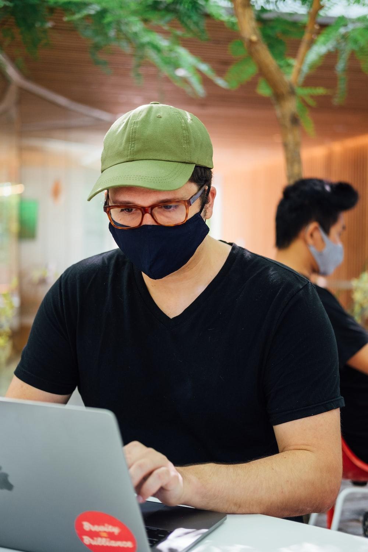 man in black crew neck t-shirt wearing green cap and black framed eyeglasses
