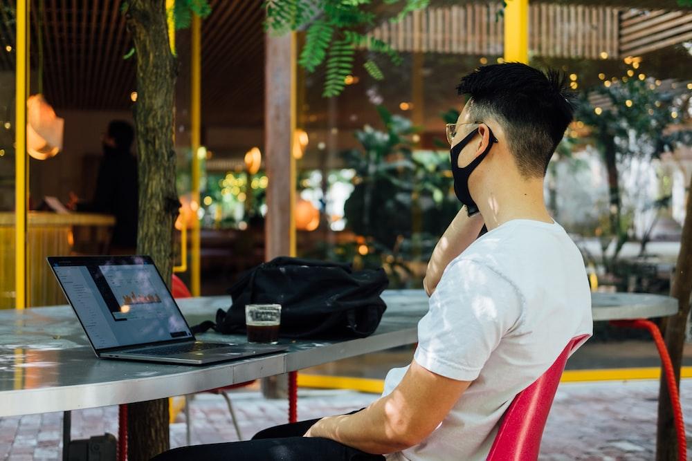 man in white t-shirt wearing black headphones sitting on chair