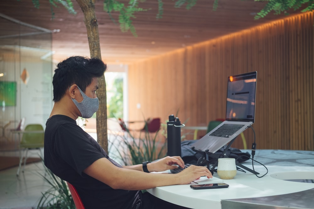 man in black t-shirt sitting in front of laptop computer
