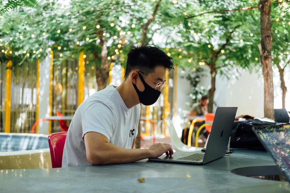 man in white crew neck t-shirt wearing black sunglasses using laptop computer