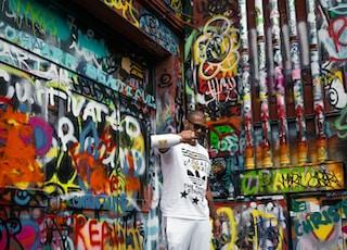 man in white t-shirt and white pants standing near graffiti wall