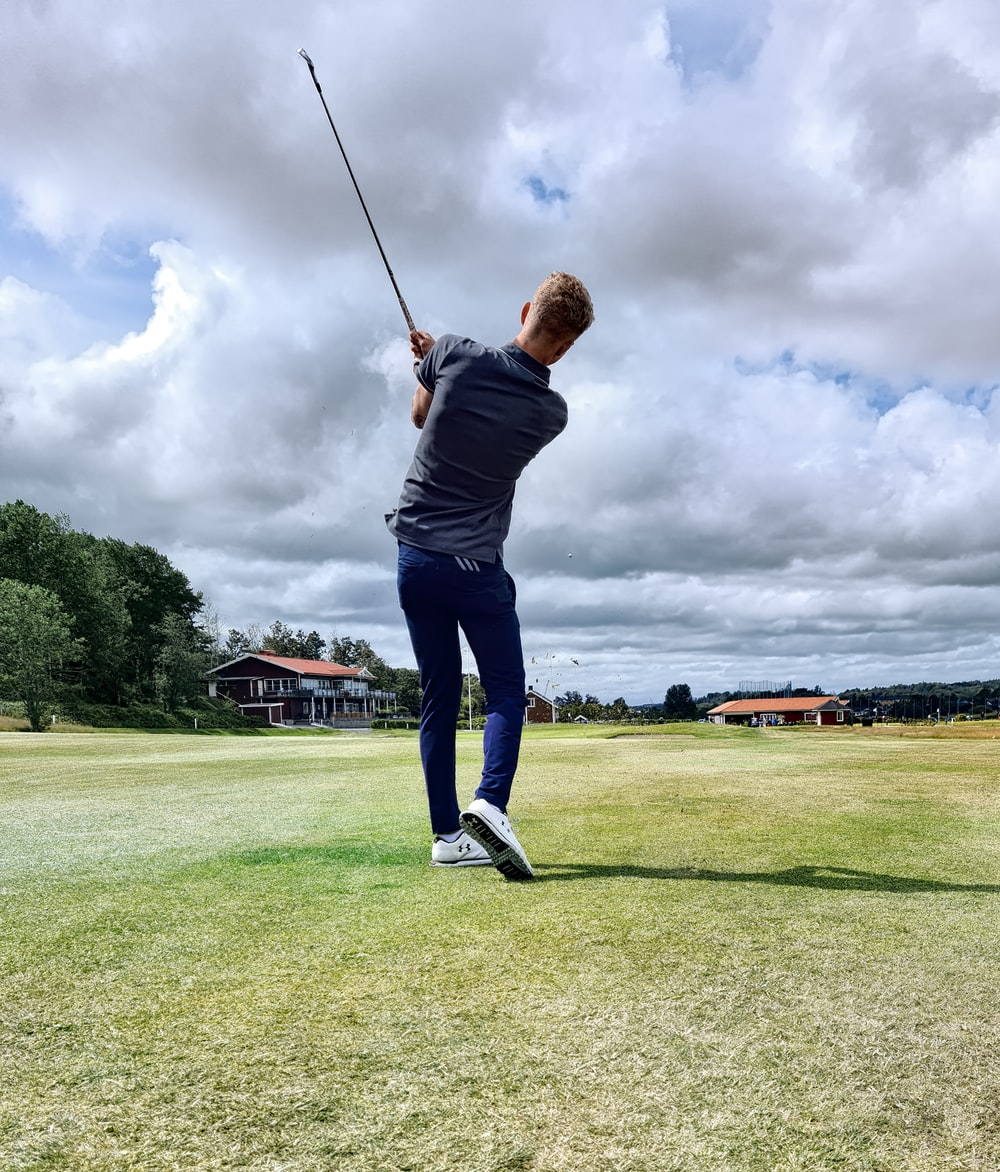 man in black shirt and blue denim jeans playing golf during daytime