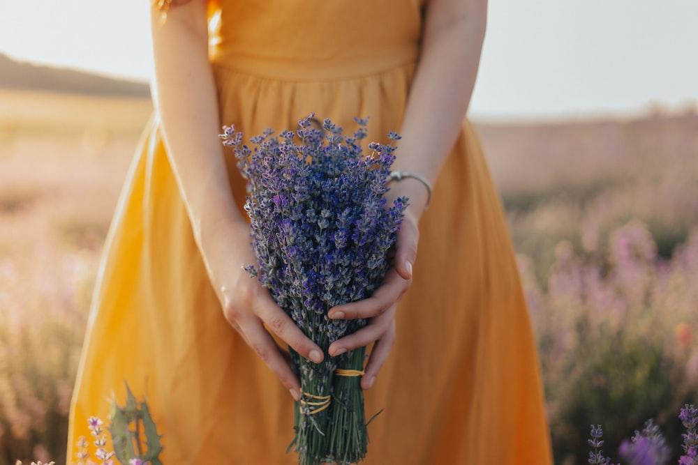 woman in yellow dress holding purple flower bouquet
