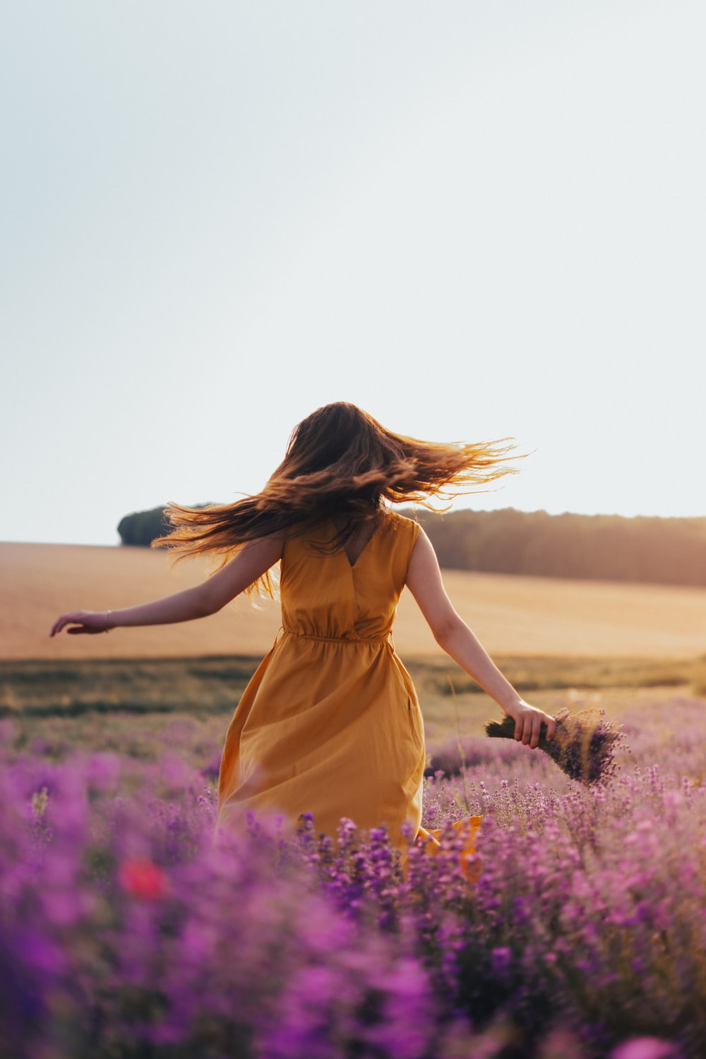 woman in yellow dress standing on purple flower field during daytime