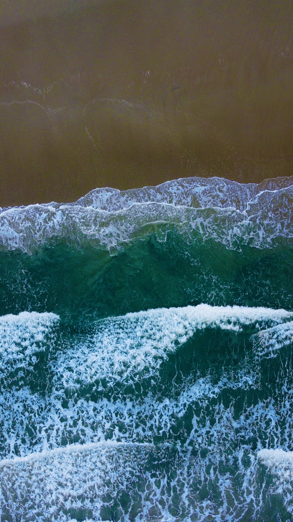 water waves on shore during daytime