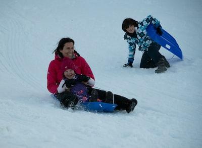 girl in pink jacket playing on snow toboggan zoom background
