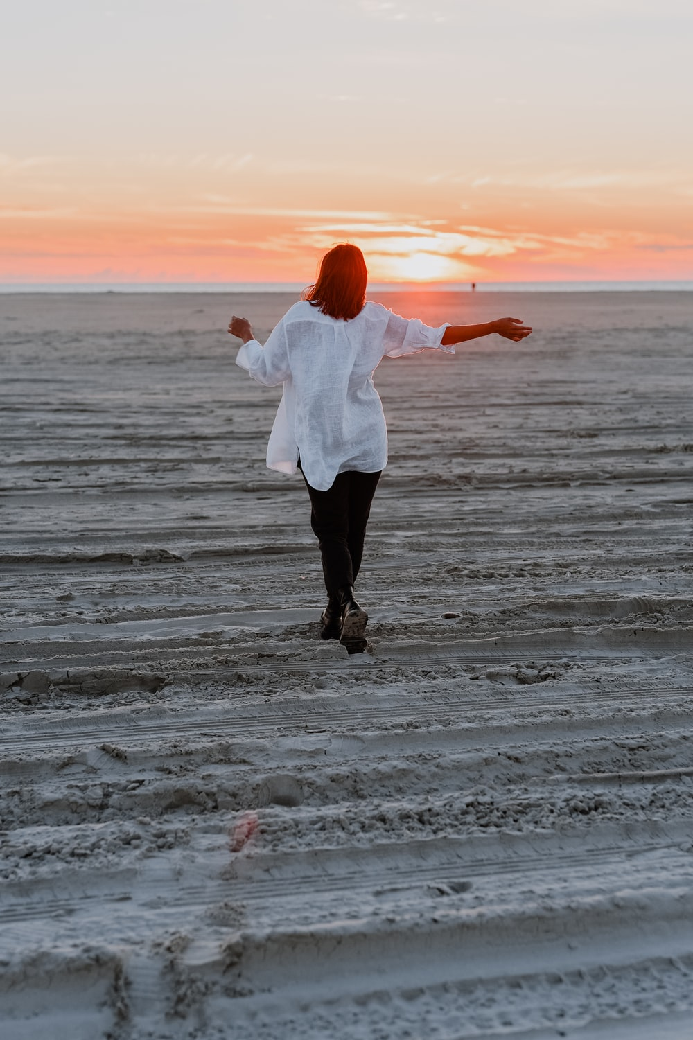 woman in white long sleeve shirt and black pants standing on beach during sunset
