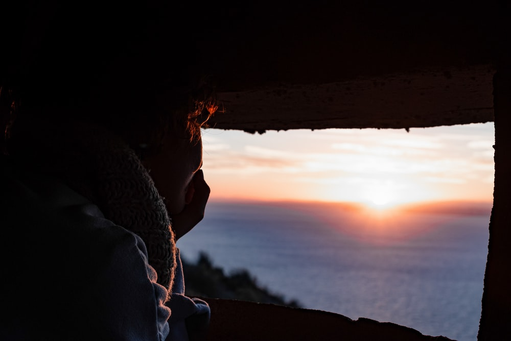 man in black jacket looking at sunset