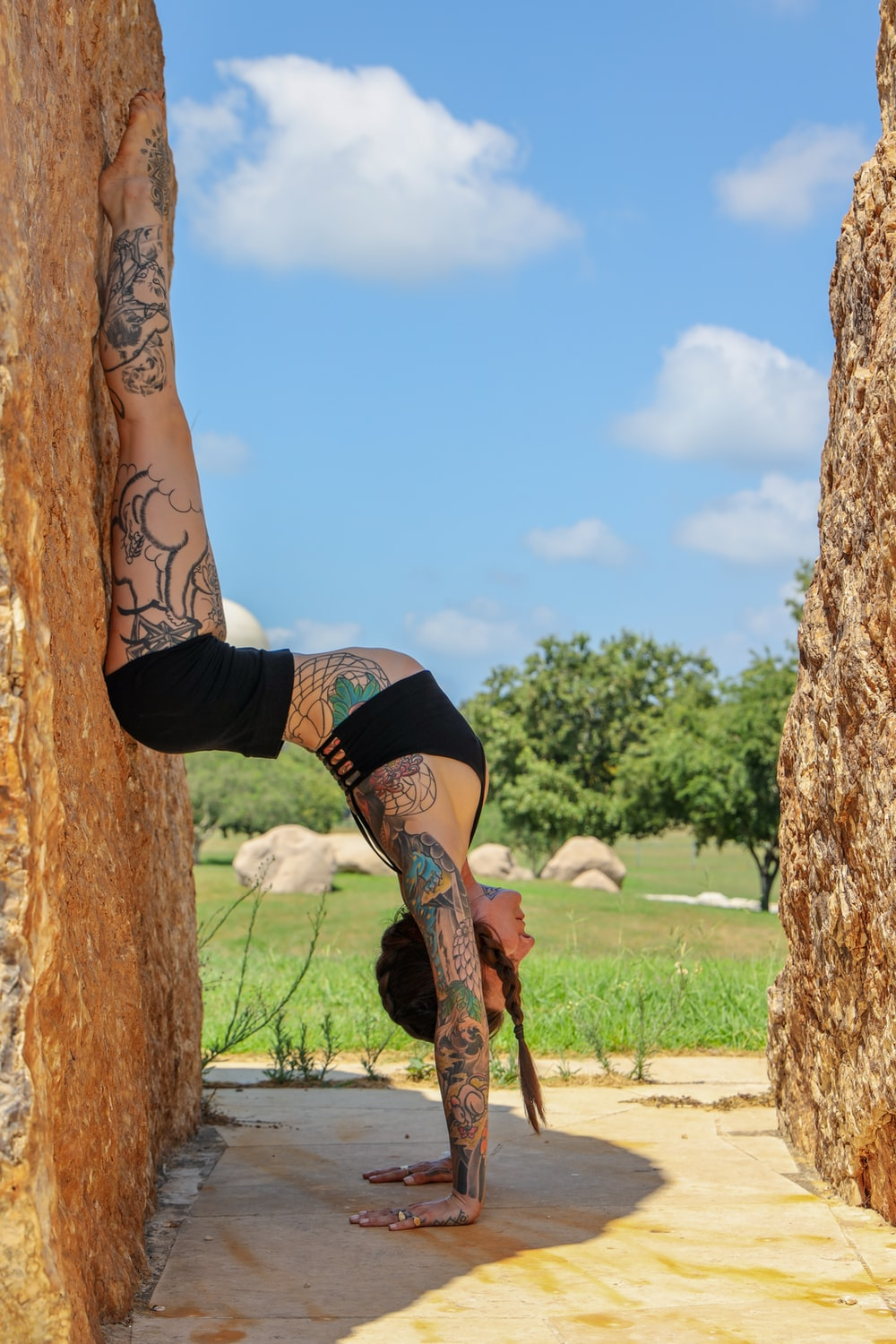 woman in black sports bra and black shorts climbing on brown tree during daytime