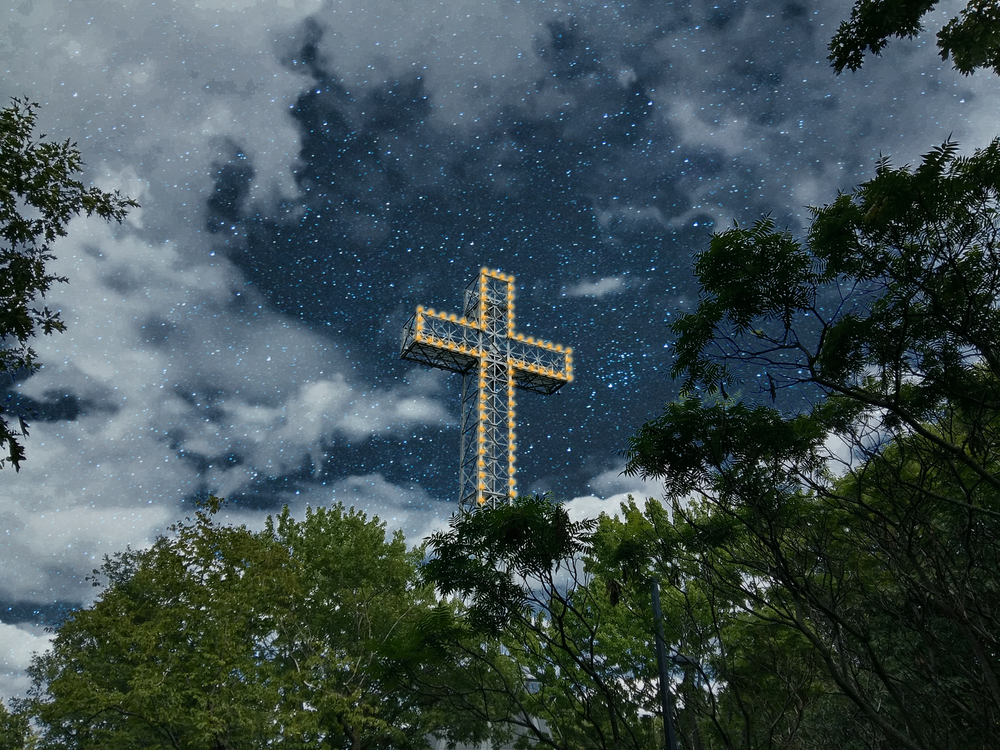 brown cross on green trees under white clouds