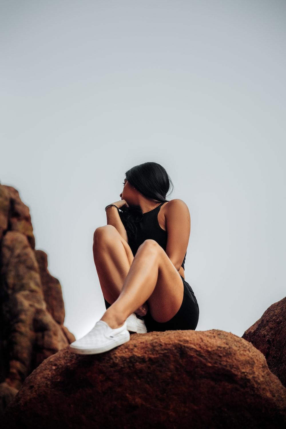 woman in black bikini sitting on brown rock during daytime