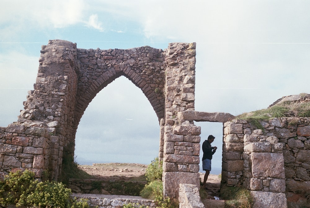 man in black shirt standing on brown arch during daytime