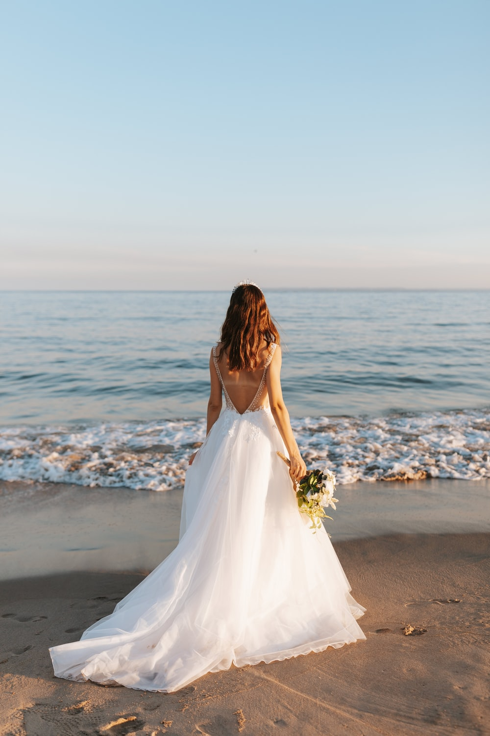 woman in white wedding dress standing on beach during daytime