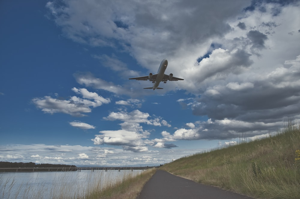 airplane flying over green grass field under blue and white cloudy sky during daytime