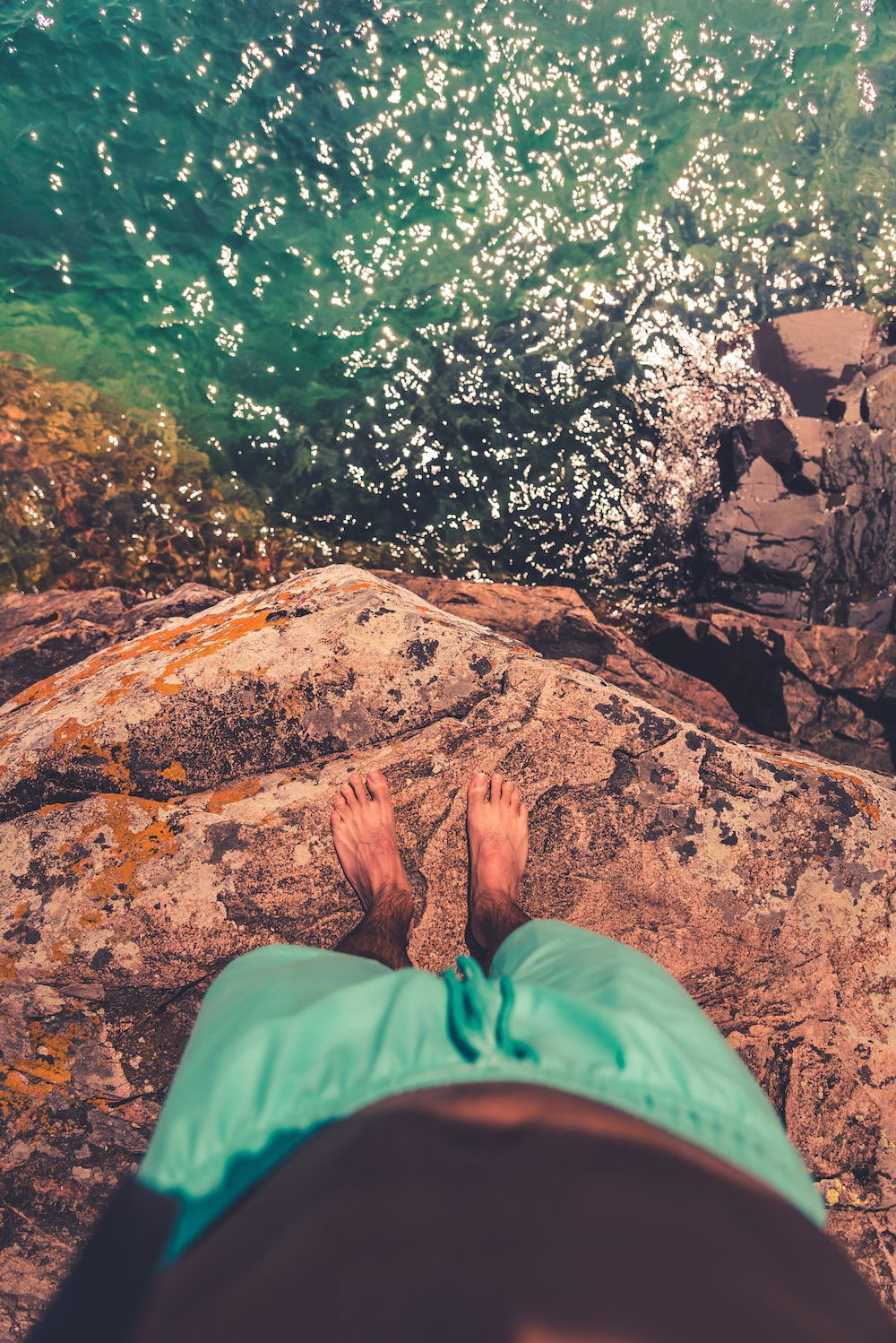 person in green pants sitting on rock near body of water during daytime