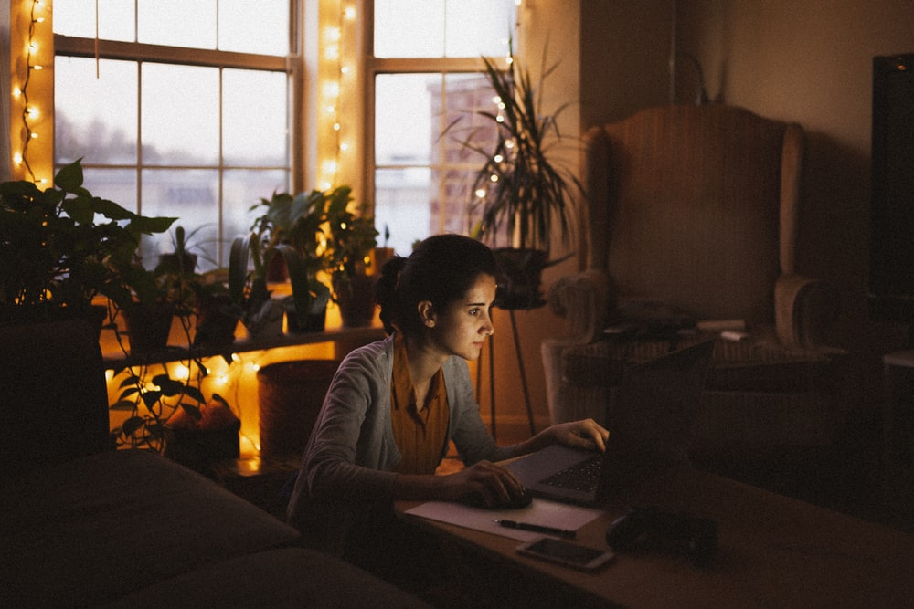 woman in gray long sleeve shirt using macbook
