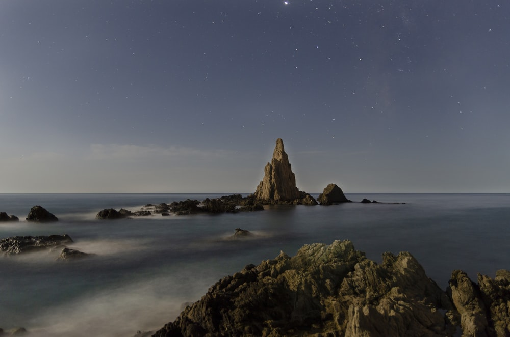 brown rock formation on sea shore during night time