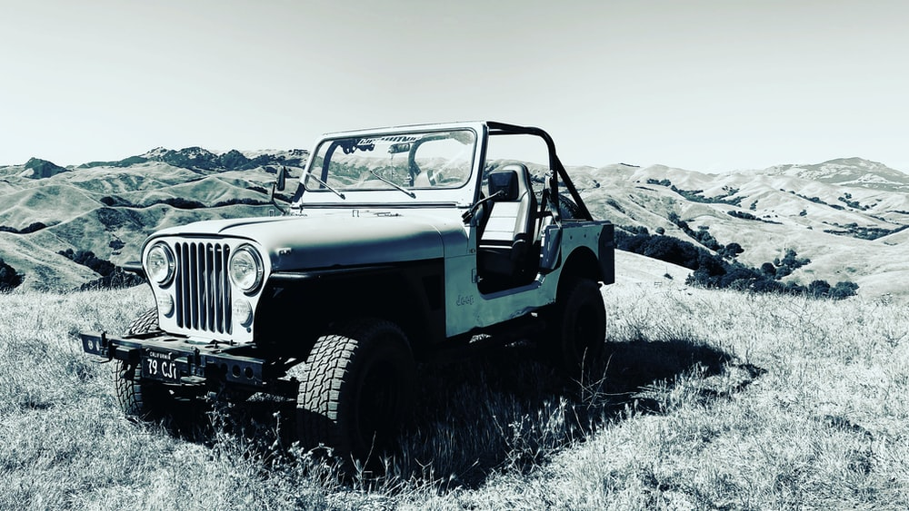 white and black jeep wrangler on gray field during daytime