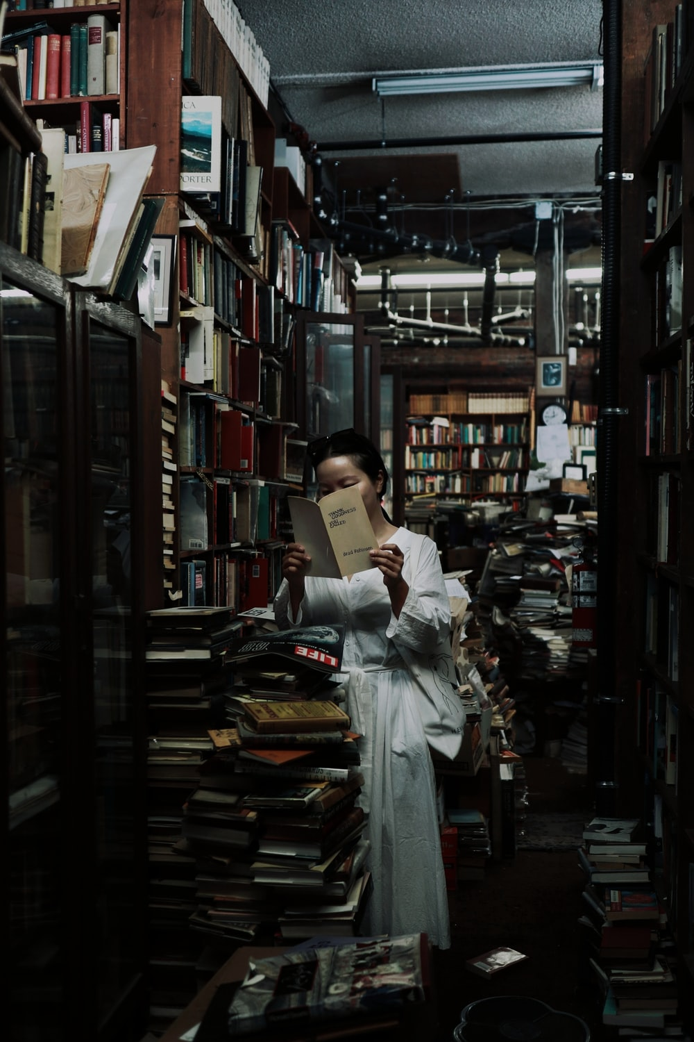 woman in white long sleeve shirt reading book in library