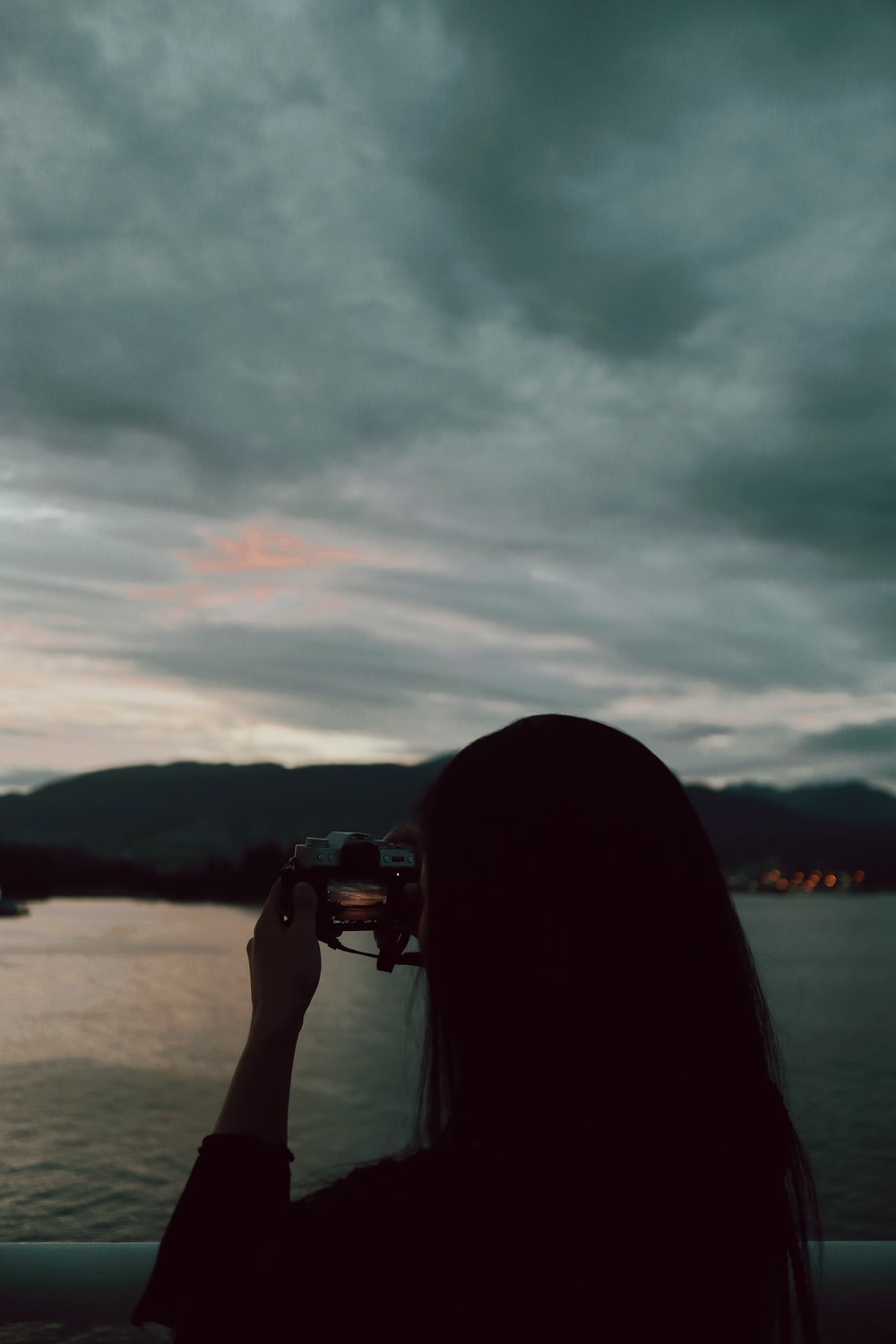 person holding black dslr camera taking photo of body of water during daytime