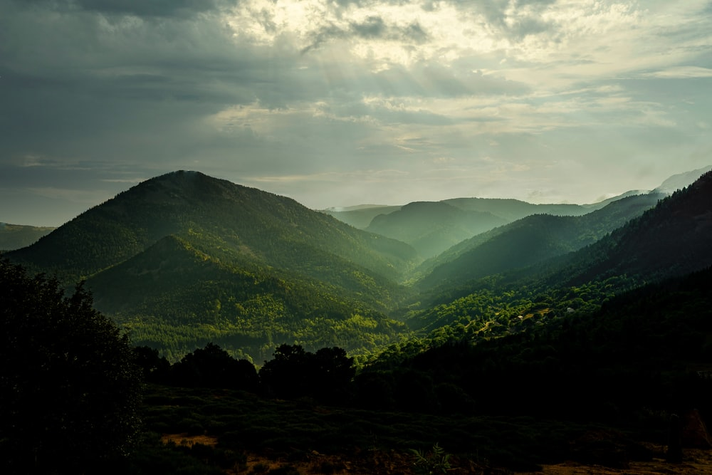 green mountains under white clouds during daytime