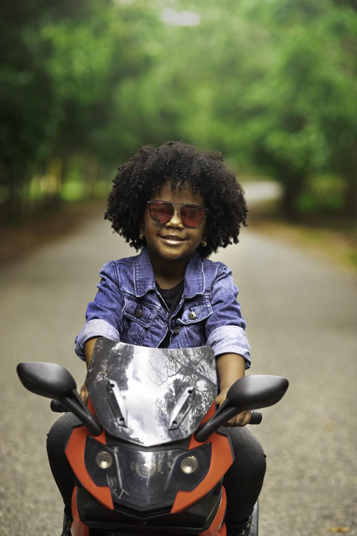 woman in blue denim jacket sitting on motorcycle