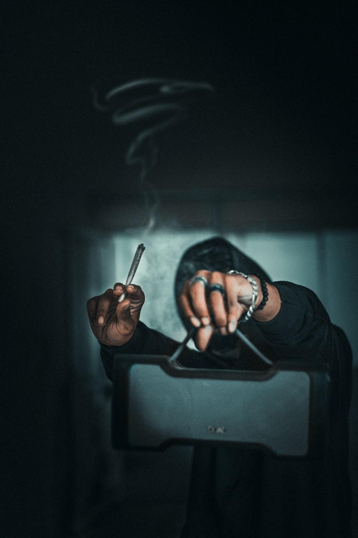 man in black long sleeve shirt smoking cigarette